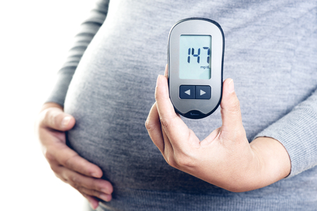 Foto per Pregnant woman checking blood sugar level with blood glucose meter. Gestational diabetes. - Immagine Royalty Free