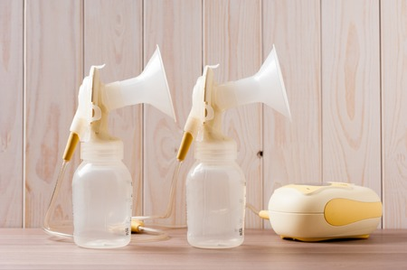 Foto de double Breast pump with blank baby bottle on wood background - Imagen libre de derechos
