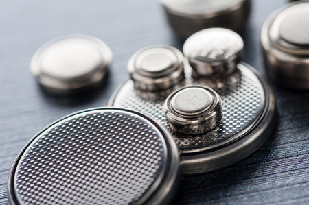 Foto de closeup button cell battery or watch battery or coin cell, used to power small electronics devices such as wrist watches or computer motherboard. - Imagen libre de derechos