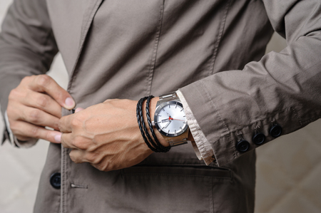 closeup the man's wrist wearing bracelets and wristwatch, casual style of men accessories.