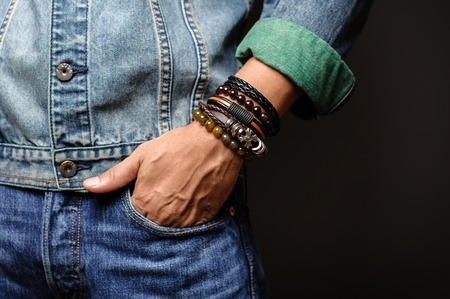 Photo for The man in jean jacket wearing bracelets, casual style of men accessories. Shallow depth of field. - Royalty Free Image