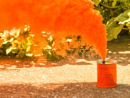 Photo pour A bright orange smoke grenade used to signal in the event of rescue or to show a position from far away. - image libre de droit