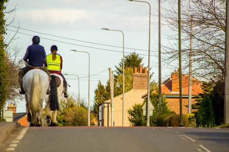 Photo for Two horse riders travel through a small village, on the main road. - Royalty Free Image