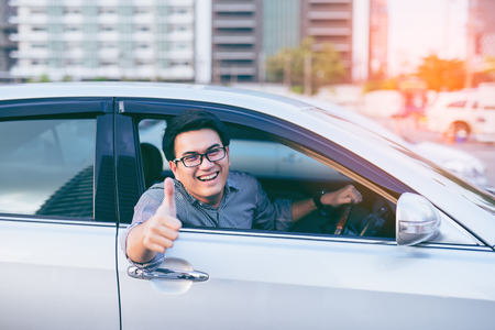 Photo for Young asian handsome man smiling and showing thumbs up in his car - Royalty Free Image