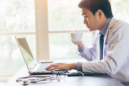 Foto de Portrait of a young handsome doctor using his laptop computer and drinking coffee with serious face - Imagen libre de derechos