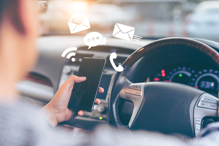 Foto de Man using smartphone while driving the car  - transportation and vehicle concept with icon social media send email wifi chat read email - Imagen libre de derechos