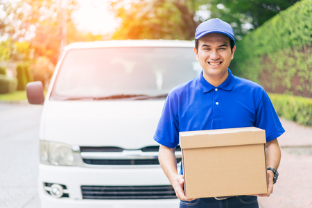 Foto de Delivery concept - Smiling happy young asian handsome man  postal delivery courier man in front of cargo van delivering package holding box with service mind and blue uniform - Imagen libre de derechos