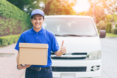 Foto de Delivery concept - Smiling happy young asian handsome man  show thumbs up and postal delivery courier man in front of cargo van delivering package holding box with service mind and blue uniform - Imagen libre de derechos