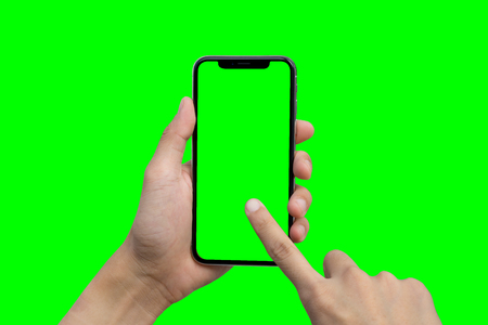 Foto de Man's hand shows mobile smartphone with green screen in vertical position isolated on green background - Imagen libre de derechos