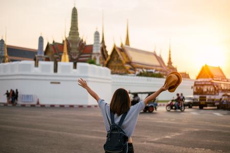 Foto de Young woman traveler travelling into Grand palace and Wat Phra Kaew at sunset Bangkok, Thailand. Amazing beautiful landmark of Bangkok Thailand. Temple of the Emerald Buddha. - Imagen libre de derechos