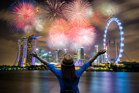 Photo pour Young woman traveler celebrate and looking view of Singapore city landmark financial district at twilight sunset scene with multicolor firework celebration. Singapore city in national day celebration. - image libre de droit