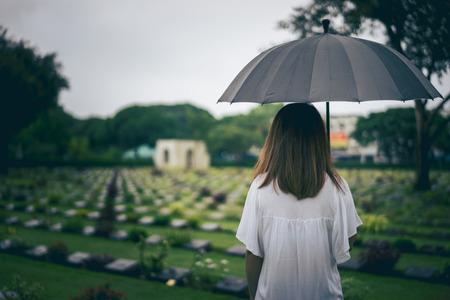 Foto de Young woman holding black umbrella mourning at cemetery - Imagen libre de derechos