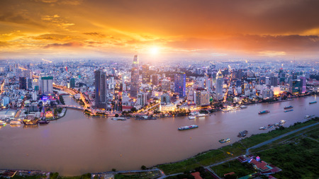 Foto de Aerial view of Ho Chi Minh City skyline and skyscrapers in center of heart business at Ho Chi Minh City downtown. Panorama of cityscape on Saigon river in Ho Chi Minh City at Vietnam at sunset scene - Imagen libre de derechos