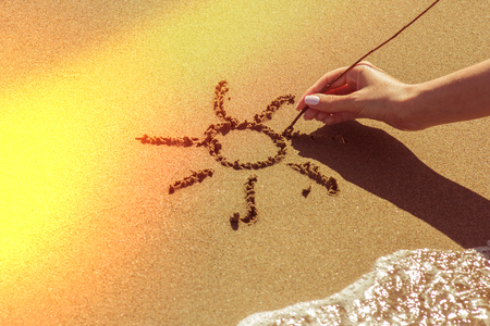 Photo for A woman's hand draws the sun on the sand by the sea, the glow effect - Royalty Free Image