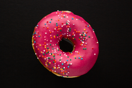 Photo for Donut pink with sprinkles isolated on black background, close-up - Royalty Free Image
