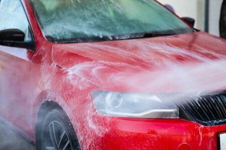Foto de Car washing. Cleaning car using high pressure water. - Imagen libre de derechos