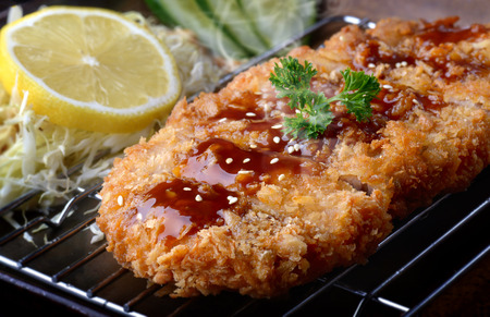 Photo for Japanese deep fried pork or tonkatsu with sauce fill on top in studio lighting. - Royalty Free Image