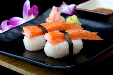 Foto de Crab stick sushi or Japanese kani sushi set on black plate with wasabi and sushi sauce with flash lighting. - Imagen libre de derechos