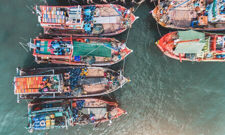 Foto de Top view from sky of group of wooden fishery boat at the sea marina with day lighting. - Imagen libre de derechos