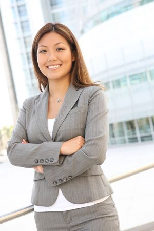 A young, pretty asian business woman at office building