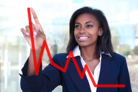 Pretty business woman drawing a graph on a glass window at office - focus is on woman