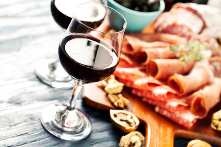 Photo pour Red wine with charcuterie assortment on the background - image libre de droit