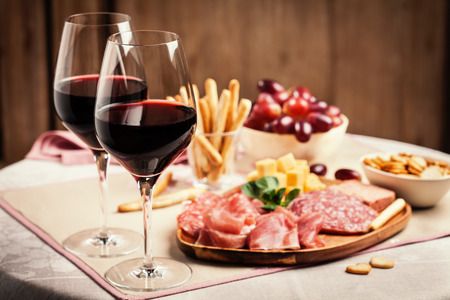 Photo pour Two glasses of red wine with charcuterie, cheese, grapes and snacks - image libre de droit