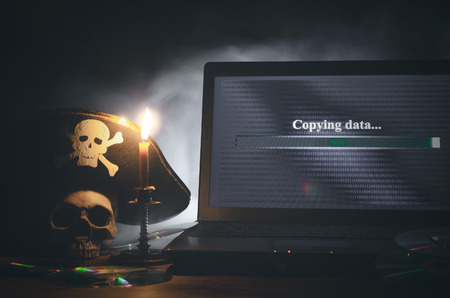 Photo for Illegal data copying concept. Cybercrime. Computer piracy background. Pirate hat, human skull, laptop and compact disc on a table. - Royalty Free Image