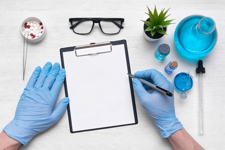 Foto de Medical examination mockup. A doctor or pharmacist is writing a notes to a blank paper sheet with a pen in his hand on laboratory table background. - Imagen libre de derechos