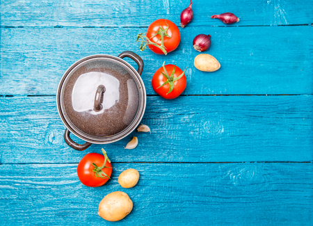 Foto de Photo on top of iron pot, tomato, potato, onion on blue wooden background. - Imagen libre de derechos