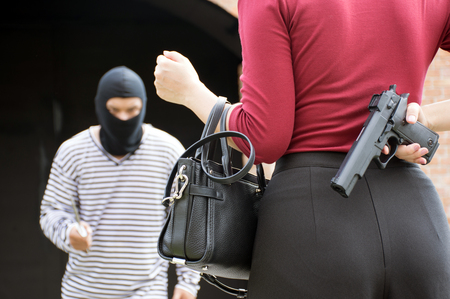 Photo for Male robber standing and looking at young woman and young woman hide gun in his back/self-defense of woman,criminal concept - Royalty Free Image