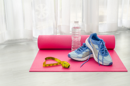 Photo pour Sport shoes, yoga mat, bottle of water and centimeter on wooden background. Sport equipment. Concept healthy life. Selective focus - image libre de droit