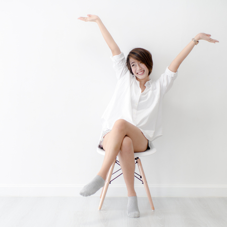 Photo for Attractive Asian girl sitting on white modern chair and relax at home. - Royalty Free Image