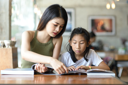 Foto de Beautyiful woman reading a book with her younger sister. - Imagen libre de derechos