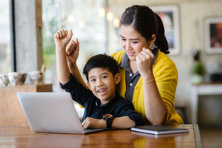 Foto de Happy Asian mother and her son raising their hands while win the online game together. - Imagen libre de derechos