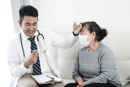 Photo pour Asian doctor checking up his patient old woman in office. - image libre de droit