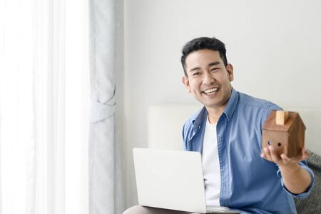 Photo pour Asian man holding house in his hand and using laptop, real estate concept. - image libre de droit