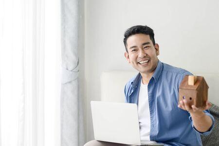 Foto de Asian man holding house in his hand and using laptop, real estate concept. - Imagen libre de derechos