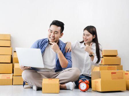 Foto de Asian couple with stack of parcel boxes, online business and delivery concept. - Imagen libre de derechos
