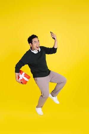 Foto de Happy Asian man holding gift box and smart phone, jumping on yellow background. - Imagen libre de derechos