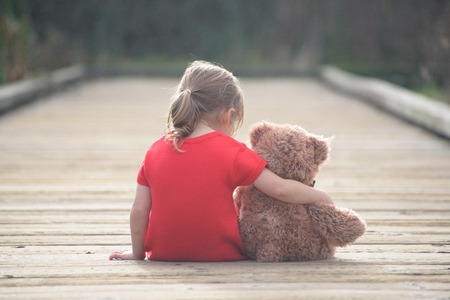 Foto de Childhood secrets are best shared with reliable friend. And if you are small sad girl teddybear is willing to be your perfect friend. - Imagen libre de derechos