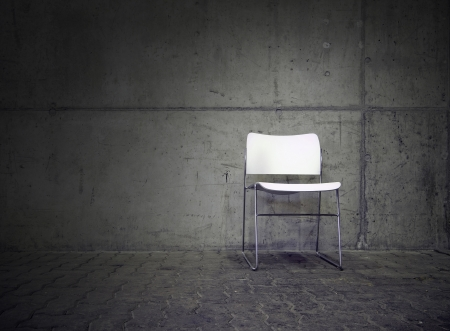white chair in spotlight with concrete wall in the background