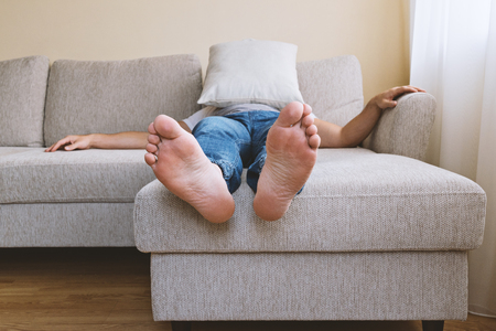 Photo for Faceless adult tired man in blue jogger jeans lying on beige sofa in depression. Men's depression concept - Royalty Free Image