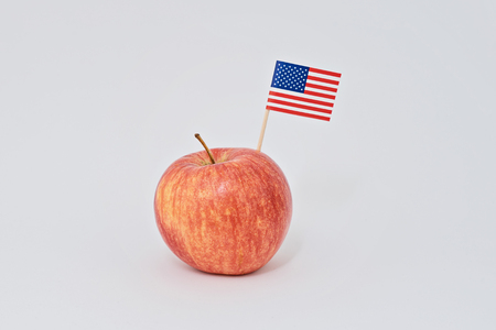Photo pour Ripe red apple and small American flag canape on white background. Greeting card for celebration of President's Day in America concept - image libre de droit