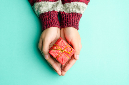Photo for Woman holding red giftbox by hand on green background - Royalty Free Image