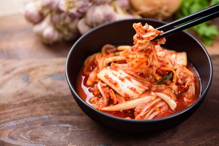 Photo pour Eating kimchi cabbage in a bowl with chopsticks, Korean food - image libre de droit