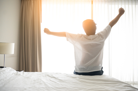 Photo for Man wake up and stretching in morning with sunlight - Royalty Free Image