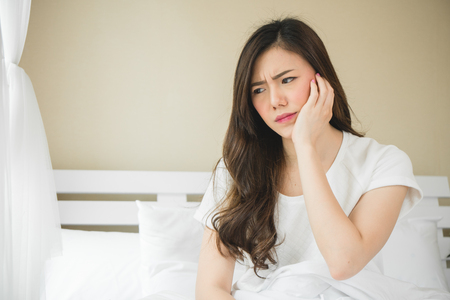 Foto de Asian woman have a toothache on white bed in white bedroom in morning - Imagen libre de derechos