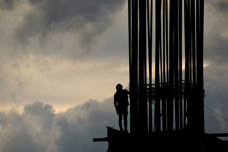 Photo pour Worker on construction site in the morning silhouette - image libre de droit