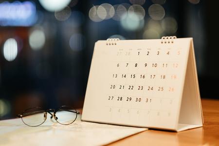 Foto de warm tone. business background calendar, glasses and travel map placed on wooden table. this image for travel, accessory, fashion, business concept - Imagen libre de derechos